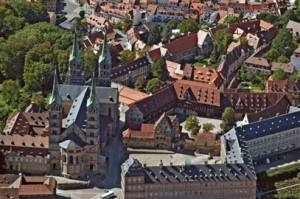 """Ein Infotisch am Domplatz, Stelen und Fahnen in den Leitfarben der Museen helfen, um den Weg in die """"Hideaways"""" Bambergs zu finden."""
